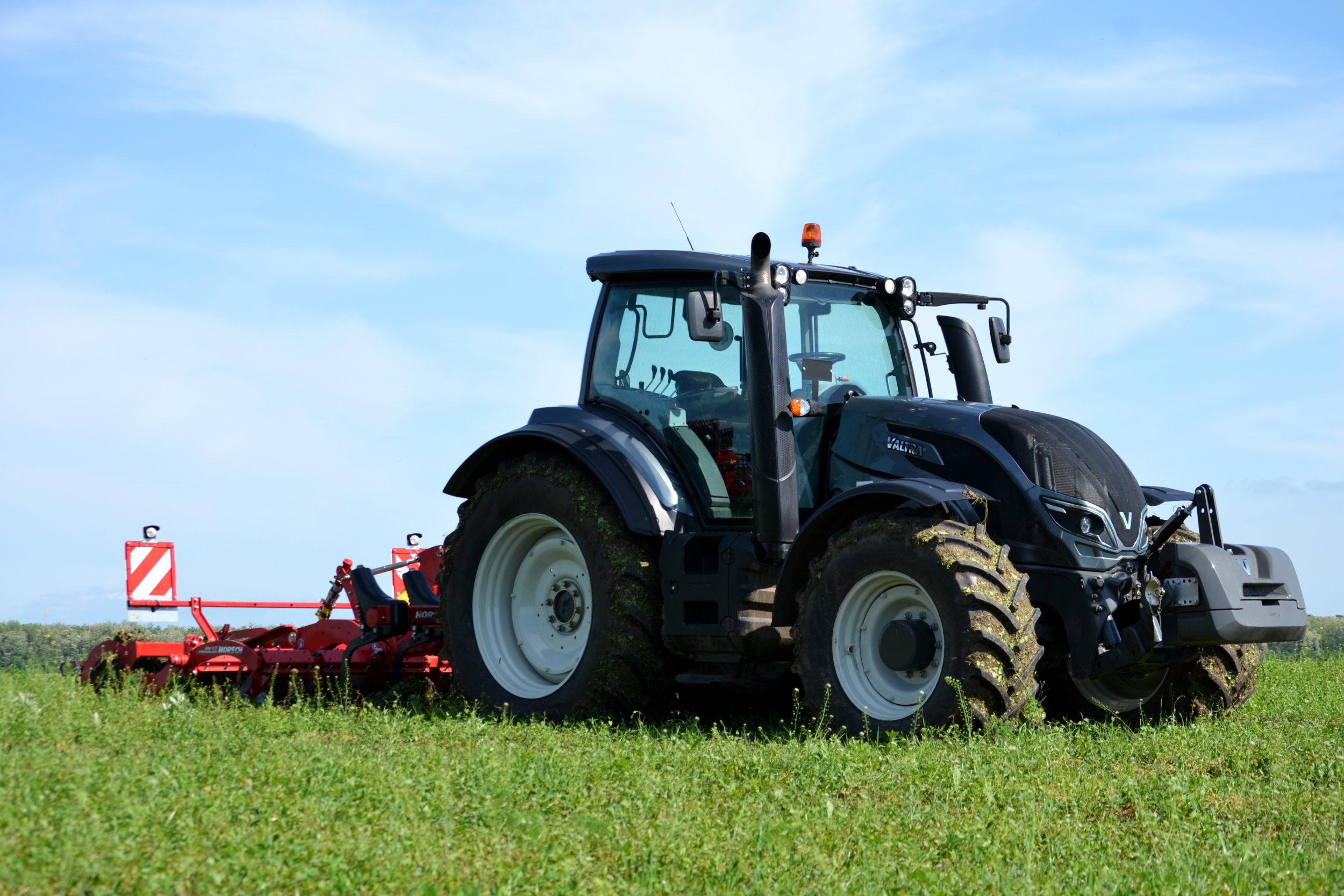 Tractor negru macra Valtra cu grapa cu discuri compacta.