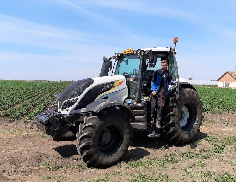 Barbat pe scara tractorului Valtra T 144 Direct in fata unui camp cultivat